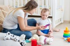 使用与她的10个月小孩男孩和教如何的美丽的少妇使用手机 库存照片