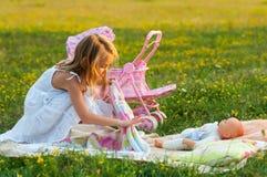 使用与她的婴孩玩具的逗人喜爱的小女孩 免版税库存照片
