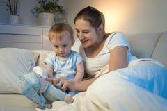 使用与她的婴孩的微笑的母亲在床上在夜和p里 库存照片