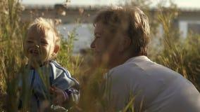 使用与她的绿色领域的小儿子的年轻愉快的母亲 影视素材