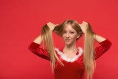 使用与她长的柔滑的头发子线的圣诞老人服装的美丽的少妇,看在红色背景的照相机 库存照片