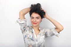 使用与她长的棕色健康卷曲结辨的头发的年轻可爱的新鲜的看起来的深色的妇女秀丽画象  情感和 库存图片