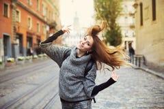 使用与她长的美丽的头发的愉快的年轻微笑的妇女 情感纵向 图库摄影