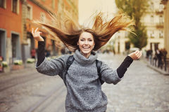 使用与她长的美丽的头发的愉快的年轻微笑的妇女 情感纵向 库存照片