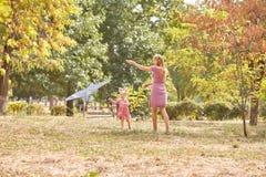 使用与妈妈的逗人喜爱的女孩,飞行在秋天公园背景的一只风筝 愉快概念的系列 复制空间 免版税库存照片