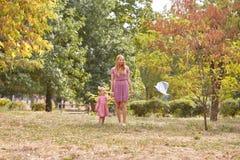 使用与妈妈的逗人喜爱的女孩,飞行在秋天公园背景的一只风筝 愉快概念的系列 复制空间 库存图片