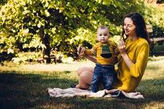 使用与婴孩的愉快的年轻母亲在有黄色枫叶的秋天公园 走户外在秋天的家庭 有h的小男孩 免版税图库摄影