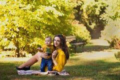 使用与婴孩的愉快的年轻母亲在有黄色枫叶的秋天公园 走户外在秋天的家庭 有h的小男孩 免版税库存照片
