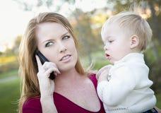 使用与子项的可爱的妇女移动电话 库存照片