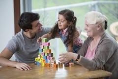 使用与字母表块的女孩由父亲和祖母在桌上在房子里 免版税库存图片