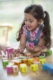 使用与字母表块的愉快的女孩在桌上 免版税库存照片