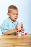 使用与字母表块的男孩 库存照片
