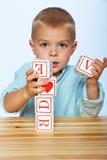 使用与字母表块的男孩 免版税库存照片