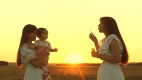 使用与孩子的愉快的母亲吹肥皂泡 女儿和母亲吹泡影在公园在日落 影视素材