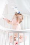 使用与它的流动玩具的尿布的愉快的婴孩在床上 免版税库存照片