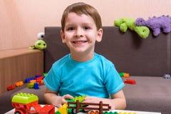 使用与室内许多的两个小白种人朋友五颜六色的塑料块 活跃孩子男孩,兄弟姐妹有乐趣修造  免版税图库摄影