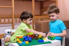 使用与室内许多的两个小白种人朋友五颜六色的塑料块 活跃孩子男孩,兄弟姐妹有乐趣修造  免版税库存图片