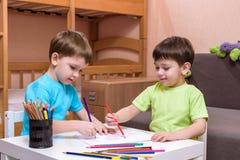 使用与室内许多的两个小白种人朋友五颜六色的塑料块 活跃孩子男孩,兄弟姐妹有乐趣修造  库存图片