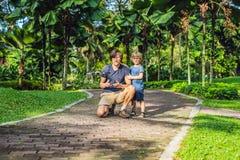 使用与寄生虫、人和男孩使用与飞行的寄生虫在晴朗的秋天庭院里,愉快的年轻男孩和父亲的爸爸和儿子 库存图片