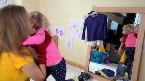 使用与小孩女孩的保姆妇女在镜子附近 股票录像