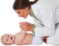 使用与小孩的愉快的女性儿科医生 免版税库存图片