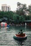 使用与小浮动充气救生艇车的公园的人们在下午 免版税库存图片