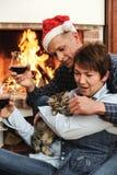 使用与小猫的男人和妇女由壁炉 免版税库存照片