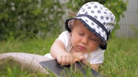 使用与小配件的女婴 孩子和新技术 使用在绿草的小孩 影视素材