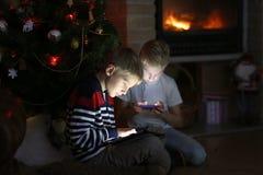 使用与小配件的两个男孩由圣诞树 免版税图库摄影