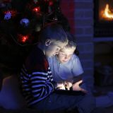 使用与小配件的两个男孩由圣诞树 免版税库存照片