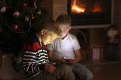 使用与小配件的两个男孩由圣诞树 库存照片