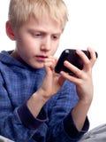 使用与巧妙的电话的男孩 免版税库存图片