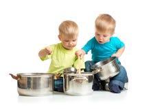 使用与平底锅的孩子,他们一起烹调 免版税图库摄影
