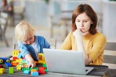 使用与建筑块的小男孩,当他的研究计算机时的母亲 免版税库存照片