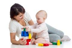 使用与建筑集合玩具一起的女婴和母亲 免版税库存图片