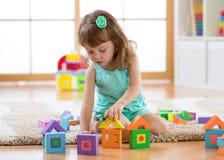 使用与建设者的儿童女孩坐地板 免版税库存照片