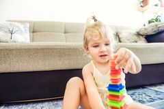 使用与建设者的逗人喜爱的小孩女婴,建造由她自己塔在家 学龄前和kindergar的教育玩具 免版税库存图片