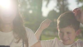 使用与弟弟的姐姐在夏天公园 户外休闲 在兄弟姐妹之间的友好的联系 股票视频