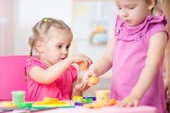 使用与彩色塑泥的小女孩在学校 库存照片