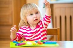 使用与彩色塑泥的小女孩 免版税库存照片