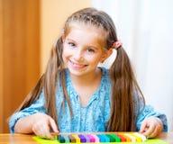 使用与彩色塑泥的小女孩 免版税库存图片