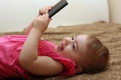 使用与您的智能手机的小微笑的孩子说谎在沙发 免版税图库摄影