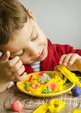 使用与意粉盘的孩子做用彩色塑泥 免版税库存图片