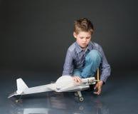 使用与手工制造平面滑翔机的孩子 举行w的青春期前的男孩 免版税库存照片