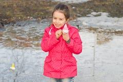 使用与手工制造船的雨靴的愉快的逗人喜爱的小女孩在春天站立在水中的小河 库存图片