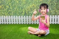 使用与手机的亚裔矮小的中国女孩 免版税库存图片