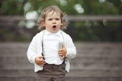 使用与手机的小女孩 免版税库存图片