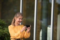 使用与手机的年轻女实业家 库存照片