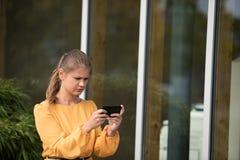 使用与手机的年轻女实业家 免版税库存照片