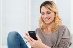 使用与手机的微笑的妇女 免版税库存照片